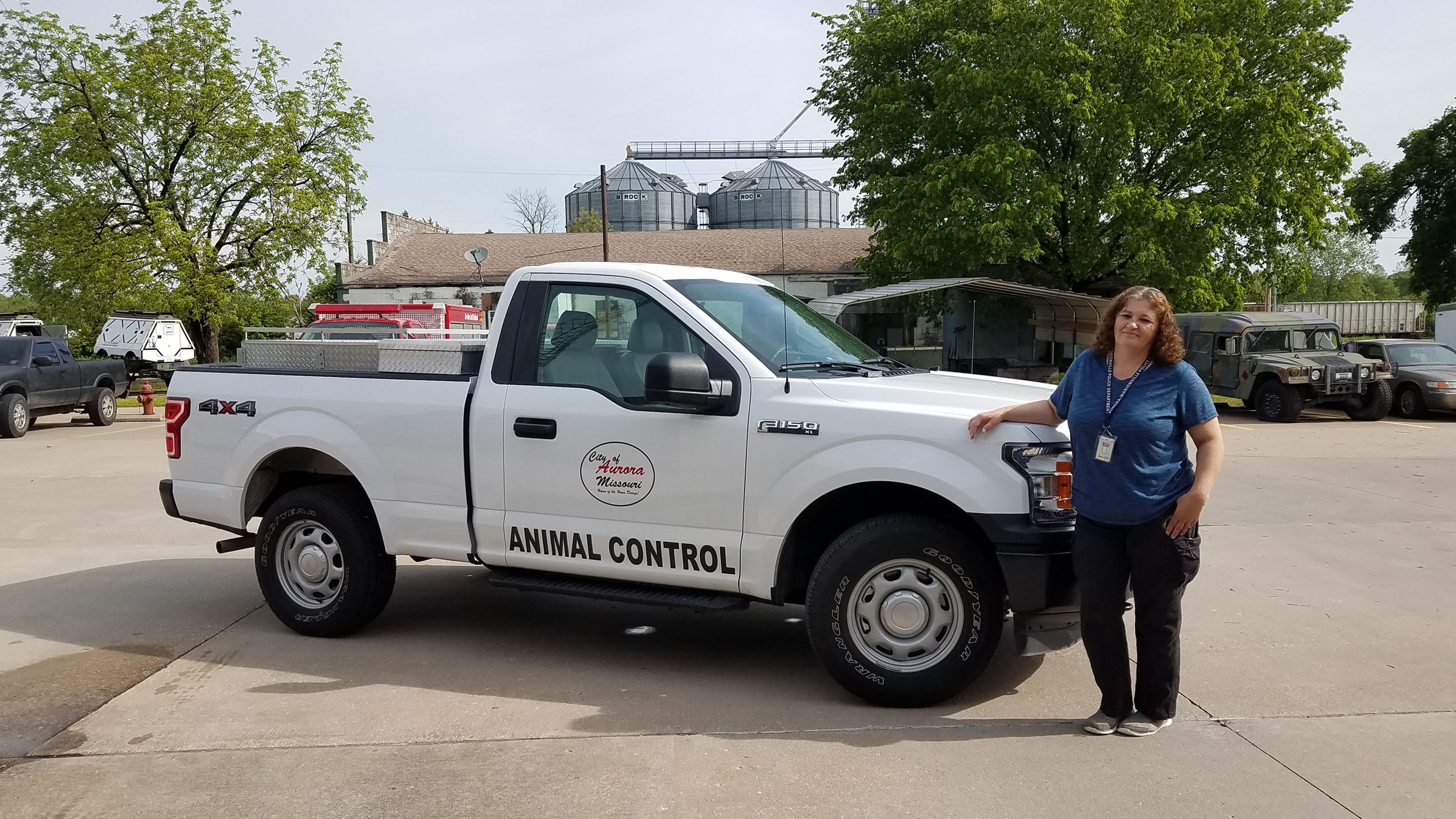 animal control officer standing in front of white pickup in parking lot